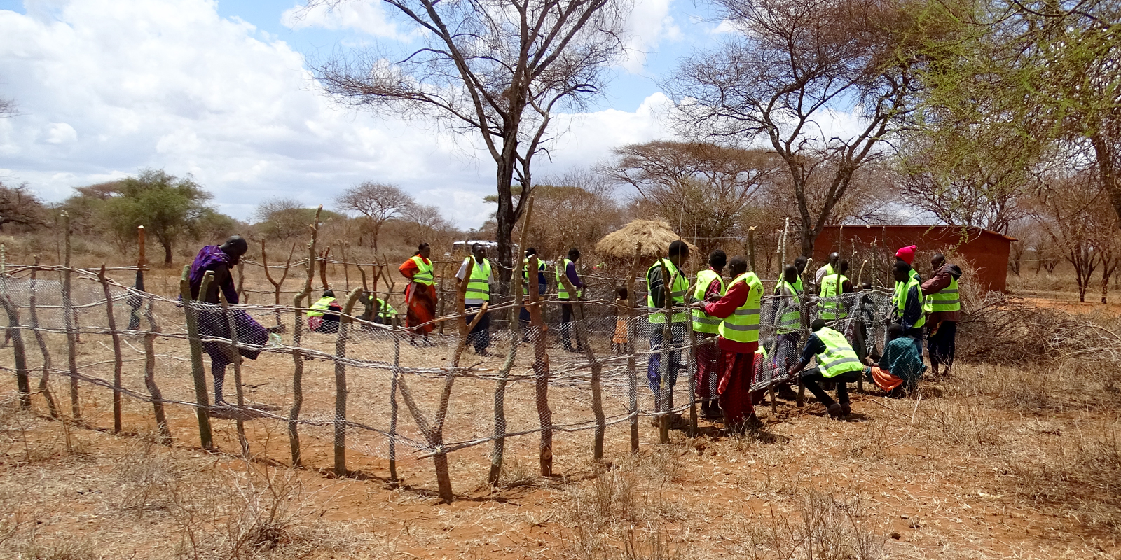 Members of MAWO and villagers building fenced-in areas for protection of donkeys